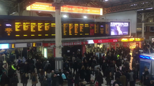 Shows interior shots large crowd of commuters waiting for Southern trains at Victoria Station in London departures boards showing cancelled trains...