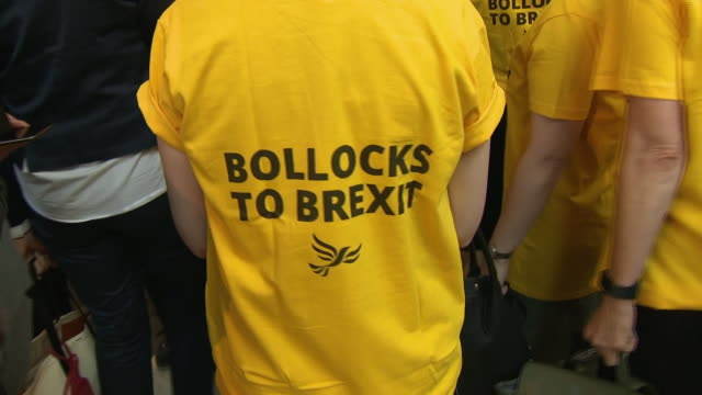shows interior shots liberal democrat meps from the uk wearing 'bollocks to brexit' tshirts as deals were done in brussels there was disruption in... - british liberal democratic party stock videos and b-roll footage