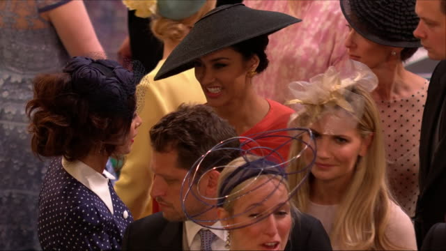 Shows interior shots Meghan's friends actress Janina Gavankar and Abigail Spencer chatting in St George's Chapel before the wedding of Prince Harry...