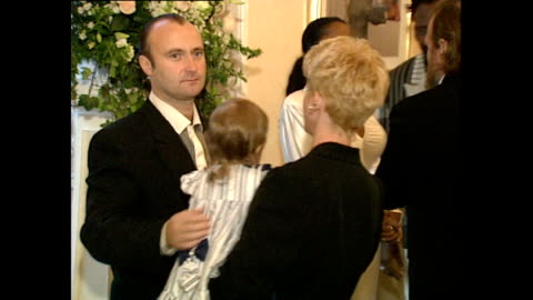 shows interior shots musician phil collins waiting with his wife jill and daughter lily to meet prince charles and princess diana at a charity rock... - フィル・コリンズ点の映像素材/bロール
