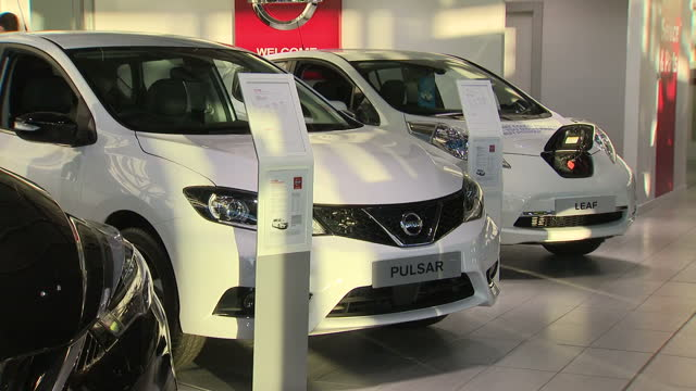 stockvideo's en b-roll-footage met shows interior shots new nissan electric cars on display in nissan car showroom including shots of inside of car and salesmen talking to customers on... - autodealer