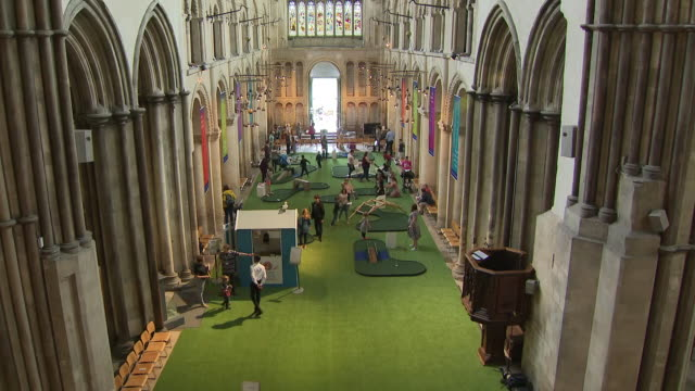 shows interior shots people playing on mini golf course set up in nave of rochester cathedral church is supposed to be a place of worship but staff... - place of worship stock videos & royalty-free footage