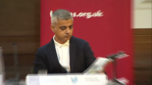 Shows interior shots police talking to hecklers and protesters as London Mayor Sadiq Khan sits reading paper on stage at Fabian Society Conference...