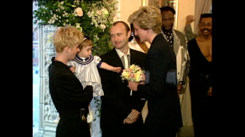 shows interior shots prince charles and princess diana meeting musician phil collins, with his wife jill and daughter lily, at a charity rock concert... - フィル・コリンズ点の映像素材/bロール