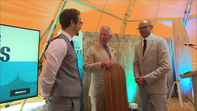shows interior shots prince charles prince of wales being presented with a surfboard on a visit to the ocean plastic solutions day organised by... - cornwall england stock-videos und b-roll-filmmaterial