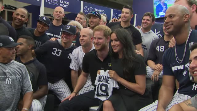 shows interior shots prince harry duke of sussex and meghan duchess of sussex posing for photo with members of the new york yankees baseball team... - サセックス点の映像素材/bロール