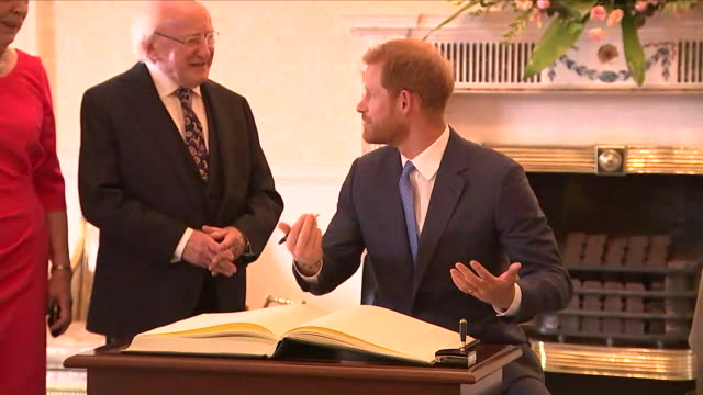 Shows interior shots Prince Harry Duke of Sussex and Meghan Duchess of Sussex signing visitor's book in the presidential mansion before posing for...