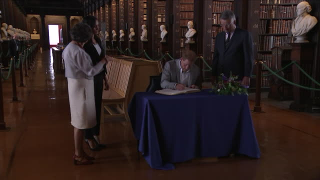 Shows interior shots Prince Harry Duke of Sussex and Meghan Duchess of Sussex signing the visitor's book on a visit to Trinity College Dublin library...