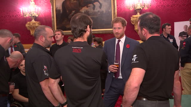 stockvideo's en b-roll-footage met shows interior shots prince harry, with beard, standing holding glass of beer talking to amputee former servicemen wearing help for heroes t-shirts... - baard