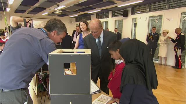 shows interior shots prince philip, duke of edinburgh, looking at examples of pupils work and asking if they aren't taught oined up writing anymore... - war stock-videos und b-roll-filmmaterial