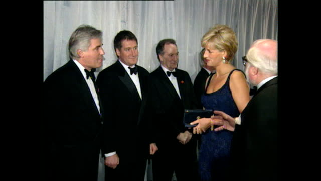 Shows interior shots Princess Diana being introduced to various members of the film crew by director Richard Attenborough at the premiere for the...