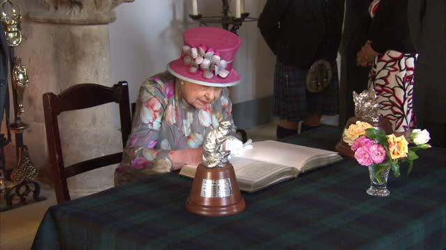 shows interior shots queen elizabeth and prince philip duke of edinburgh signing visitors book inside stirling castle the queen and prince philip... - スコットランド スターリング点の映像素材/bロール