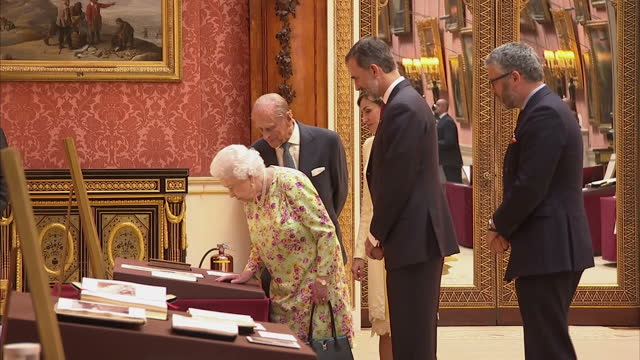 shows interior shots queen elizabeth ii and king felipe of spain looking at items from the royal collection laid out on tables and joined by queen... - philip ii of spain stock videos and b-roll footage