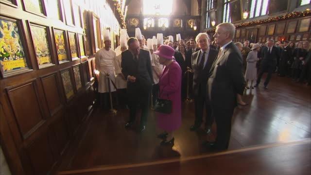 shows interior shots queen elizabeth ii and prince andrew, duke of york looking at heraldic badges in the new hall . the queen and duke of york visit... - vapen bildbanksvideor och videomaterial från bakom kulisserna