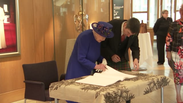 shows interior shots queen elizabeth ii and prince charles, prince of wales, signing the visitor's book at a reception at holyrood, the scottish... - signierstunde stock-videos und b-roll-filmmaterial