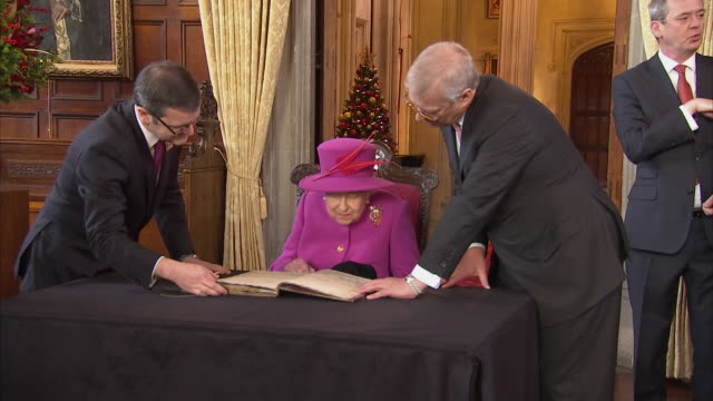 shows interior shots queen elizabeth ii being shown names in visitors book before she and prince andrew duke of york add their own signatures the... - königin elisabeth ii. von england stock-videos und b-roll-filmmaterial