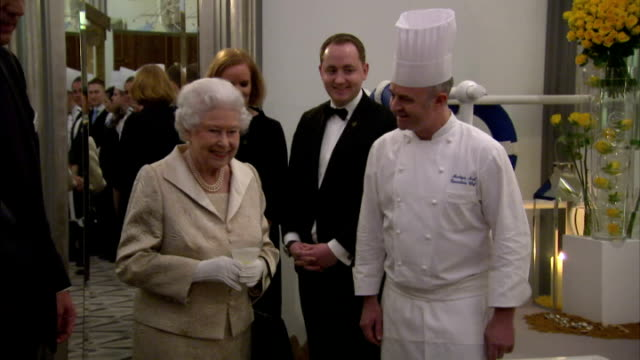 Shows Interior shots Queen Elizabeth II of Great Britain greeting various guests and viewing display of work by people in the Service industry The...