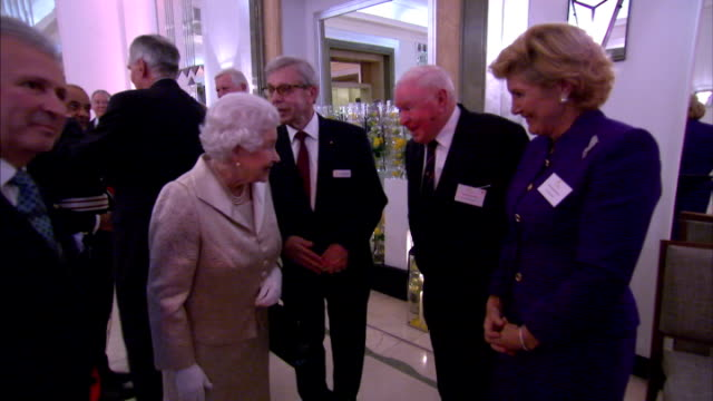 shows interior shots queen elizabeth ii of great britain shaking hands and talking to various dignitaries and guests, the queen will attend the gold... - claridge's stock videos & royalty-free footage