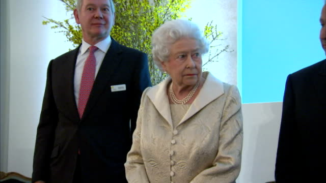 shows interior shots queen elizabeth ii of great britain walking to sit on stage at front of room, listening to speeches, presenting awards to... - claridge's stock videos & royalty-free footage
