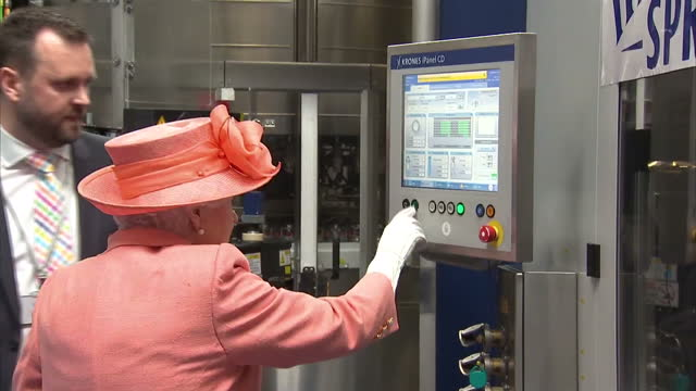 Shows interior shots Queen Elizabeth II talking to Bryan McCluskey and pressing button to start production line on tour of the new Highland Spring...