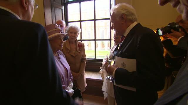 Shows interior shots Queen Elizabeth II talking to various dignitaries including British Politician John Major and actrees Dame Judi Dench at...