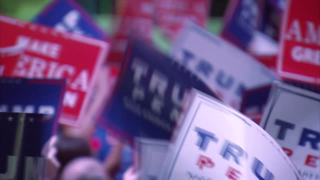 Shows interior shots Republican Presidential Candidate Donald Trump on stage at rally in Jackson Mississippi with people in crowd waving Trump signs...