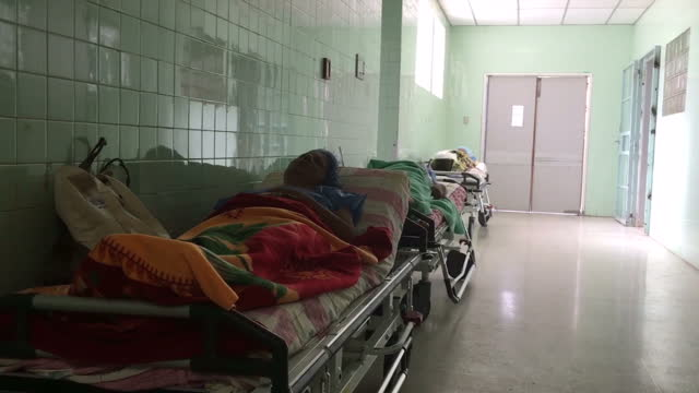 shows interior shots sick patients sitting waiting in hospital corridors, ill patients lying in beds in corridors and basic hospital wards, interior... - venezuela stock videos & royalty-free footage