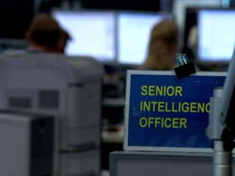 shows interior shots signage at desk & employees working at computers. on january 16, 2015 in cheltenham, england. - mi6 stock-videos und b-roll-filmmaterial