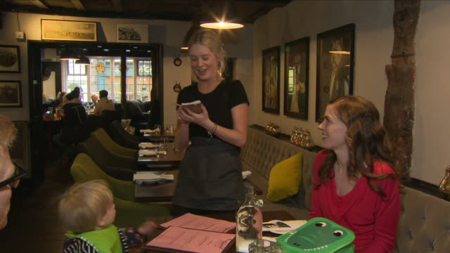 shows interior shots teenagers working in the restaurant as waitresses and as maids in the hotel in the rose and crown in knutsford. interviews with... - part time worker stock videos & royalty-free footage