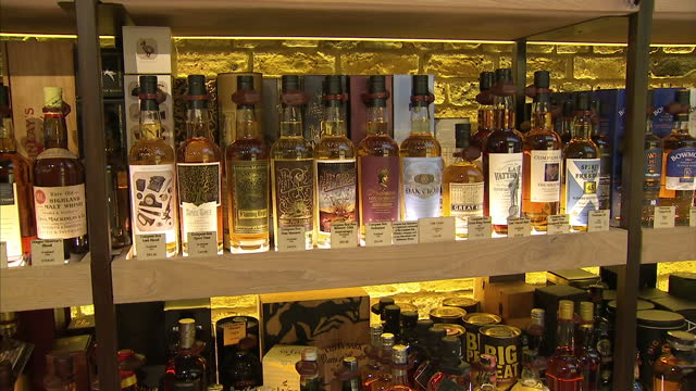 vídeos de stock e filmes b-roll de shows interior shots the compass box peat monster scottish whisky scotch for sale in shop on shelves with other bottles for sale on january 19 2015... - símbolo ortográfico