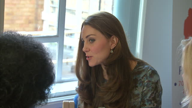 Shows interior shots the Duchess of Cambridge sat with guests at table listening talking with them on January 19 2015 in London England