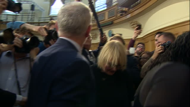 shows interior shots uk labour party leader jeremy corbyn surrounded by supporters and media making his way out of assembly hall after giving his... - circondare video stock e b–roll