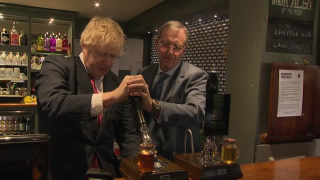 shows interior shots uk prime minister boris johnson pulling a pint and posing for photos with newly elected conservative party mps paul howell... - pint glass stock videos & royalty-free footage