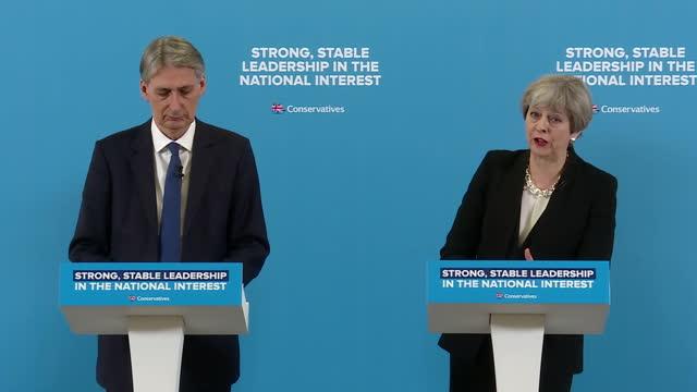 Shows interior shots UK Prime Minister Theresa May and UK Chancellor Philip Hammond standing at podium during press conference and Theresa May...