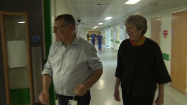 Shows interior shots UK Prime Minister Theresa May walking down hospital corridor with official as she visits Frimley Park Hospital The Prime...