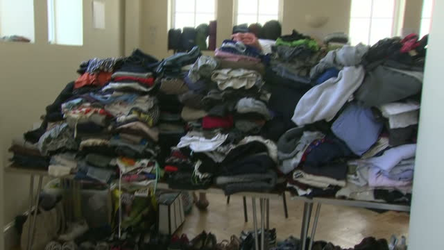 shows interior shots volunteers sorting piles of clothes donated for victims of the grenfell tower block fire a huge fire tore through a 24 storey... - charitable donation stock videos & royalty-free footage