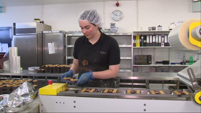 shows interior shots women working in a sweet making factory production line prepared weets being placed on plastic trays covered in cellophane and... - cellophane stock videos & royalty-free footage