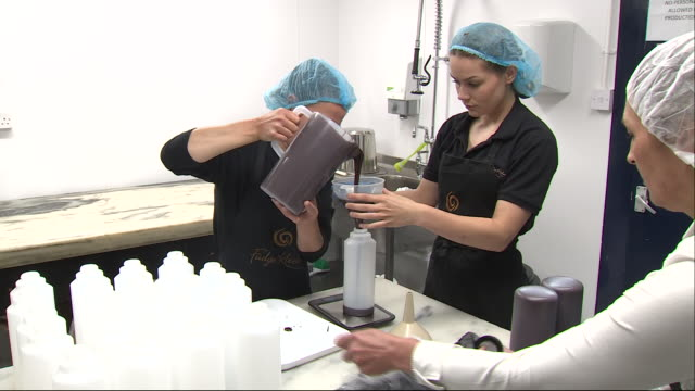 shows interior shots women working in a sweet making factory, taking melted chocolate from a vat and pouring it into bottles. the governor of the... - creazione video stock e b–roll
