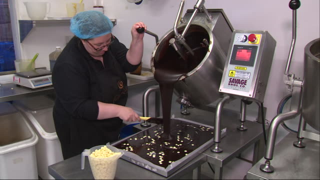 shows interior shots women working in a sweet making factory, woman pouring melted chocolate from vat onto tray, and sprinkling nuts or white... - sprinkling stock videos & royalty-free footage