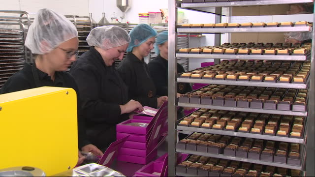 shows interior shots women working in a sweet making factory women on production line receiving cellophane wrapped trays of cfudge placing them in... - cellophane stock videos & royalty-free footage