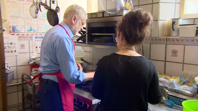 shows labour leader jeremy corbyn helping with cooking at a community centre in shipley west yorkshire on 12th october 2017 - west yorkshire stock-videos und b-roll-filmmaterial