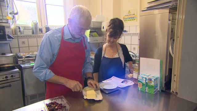 shows labour leader jeremy corbyn helping with cooking at a community centre in shipley west yorkshire on 12th october 2017 - jeremy corbyn stock-videos und b-roll-filmmaterial