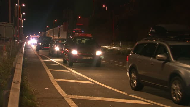 shows night shots police car driving alongside long queue of traffic on motorways leading to port of dover with cars stopped and shot of child... - dover kent stock-videos und b-roll-filmmaterial