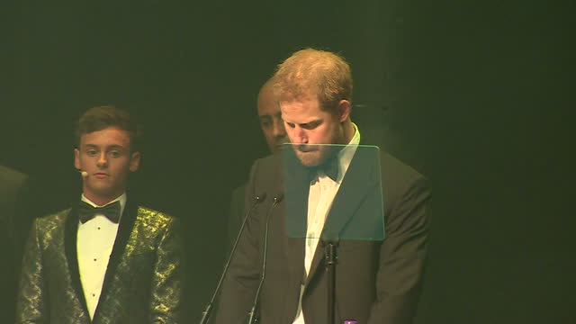 Shows Prince Harry accepting posthumous Attitude Legacy Award on behalf of his mother Diana Princess of Wales for her work in HIV and Aids activism...