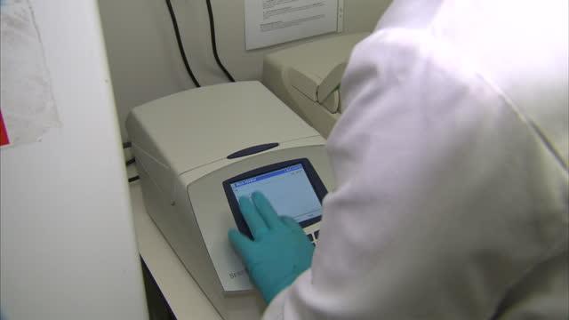 vídeos de stock, filmes e b-roll de shows purple samples in petri dish lab technician placing samples into analysing machine screen w/ lab technician programming device on april 01 2014... - ébola