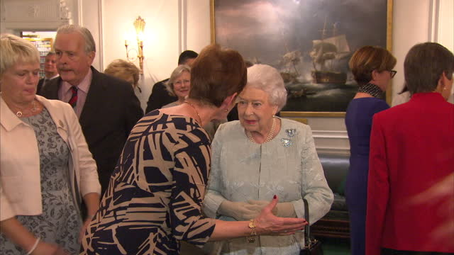 Shows Queen Elizabeth II chatting to people at a reception to mark the Centenary of the Women's Royal Navy Service and the Women's Auxiliary Army...