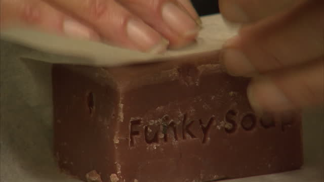 shows staff member at funky soap shop workshop warpping soap in packaging in london on october 9th 2017 - sapone video stock e b–roll