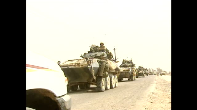 shows us military convoy at a standstill on road in southern baghdad and a military vehicle driving past. various iraqi people stand nearby. - イラク点の映像素材/bロール