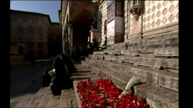 shows various candles on steps of perugia cathedral as well as various people relaxing on steps in perigia on 8th november 2007 - ウンブリア州点の映像素材/bロール