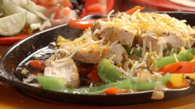 CU shredded cheese sprinkled over seared pieces of chicken breast in fajita pan sizzling with slices of bell peppers in hot cooking oil
